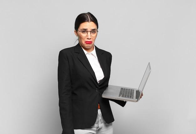 Mulher jovem e bonita se sentindo triste e chorona com um olhar infeliz, chorando com uma atitude negativa e frustrada. conceito de laptop