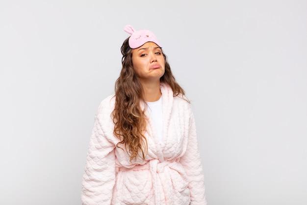 Mulher jovem e bonita se sentindo triste e chorona com um olhar infeliz, chorando com uma atitude negativa e frustrada de pijama