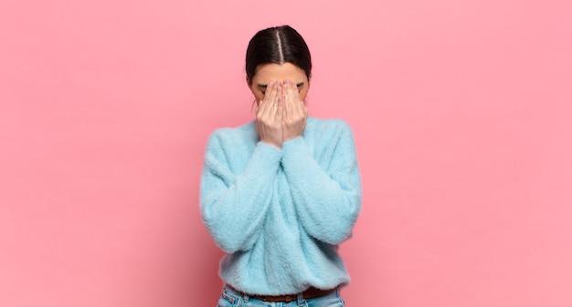 Mulher jovem e bonita se sentindo triste, frustrada, nervosa e deprimida, cobrindo o rosto com as duas mãos, chorando