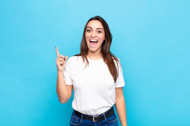 Mulher jovem e bonita se sentindo um gênio feliz e animado depois de realizar uma idéia, alegremente levantando o dedo, eureka! contra a parede azul