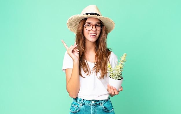 Mulher jovem e bonita se sentindo um gênio feliz e animado depois de realizar uma ideia com um chapéu de palha e segurando um cacto