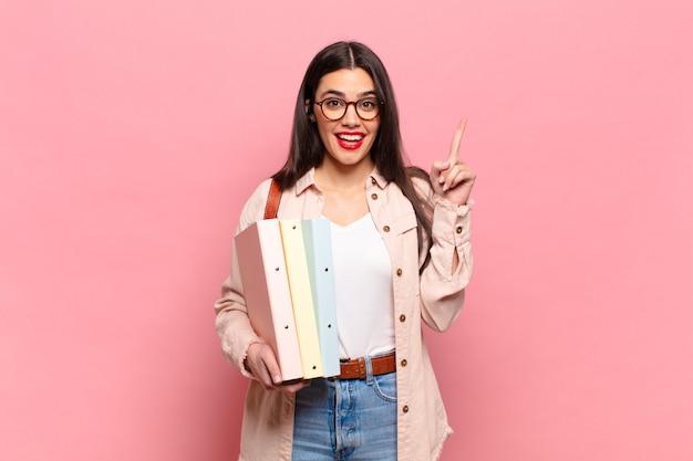 Mulher jovem e bonita se sentindo um gênio feliz e animado depois de realizar uma ideia, levantando o dedo alegremente, eureka !. conceito de estudante