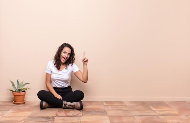 Mulher jovem e bonita se sentindo um gênio feliz e animado depois de realizar uma ideia, levantando o dedo alegremente, eureka! sentado no chão do terraço