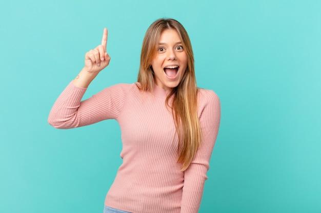 Mulher jovem e bonita se sentindo um gênio feliz e animado depois de realizar uma ideia