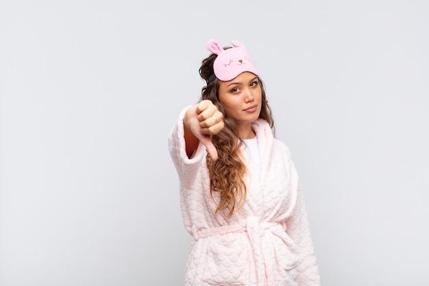 Mulher jovem e bonita se sentindo zangada, irritada, aborrecida, decepcionada ou descontente, mostrando os polegares para baixo com uma expressão séria de pijama