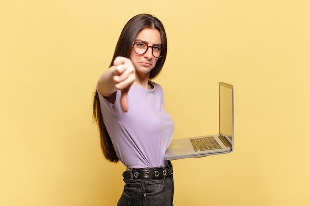 Mulher jovem e bonita se sentindo zangada, irritada, decepcionada ou descontente, mostrando os polegares para baixo com um olhar sério. conceito de laptop