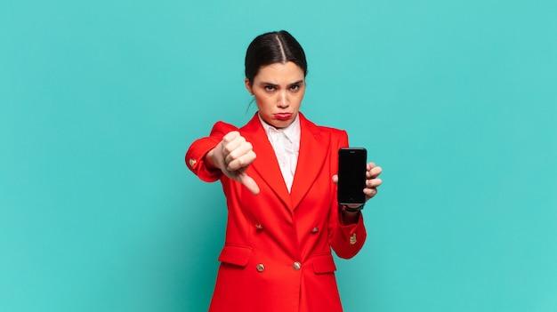 Mulher jovem e bonita se sentindo zangada, irritada, decepcionada ou descontente, mostrando os polegares para baixo com um olhar sério. conceito de telefone inteligente