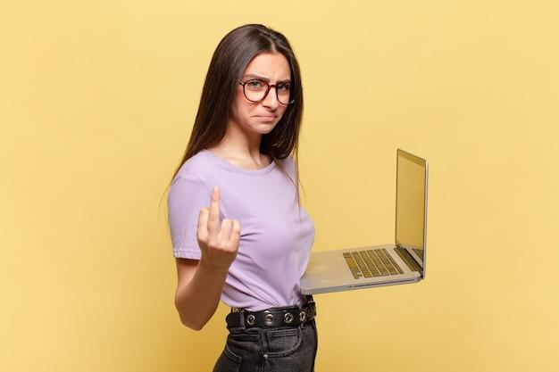 Mulher jovem e bonita se sentindo zangada, irritada, rebelde e agressiva, sacudindo o dedo do meio, lutando de volta. conceito de laptop