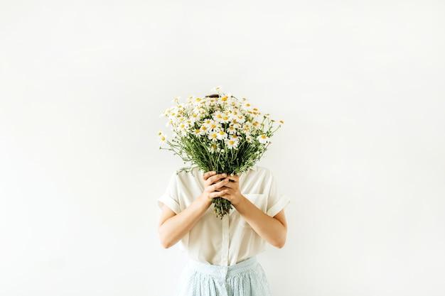 Mulher jovem e bonita segura nas mãos o buquê de flores da margarida de camomila branca em branco.