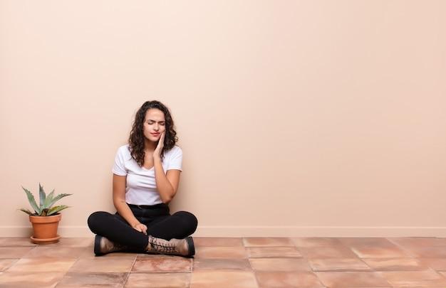 Mulher jovem e bonita segurando a bochecha e sofrendo de uma dor de dente dolorosa, sentindo-se doente, infeliz e infeliz, procurando um dentista sentado no chão do terraço