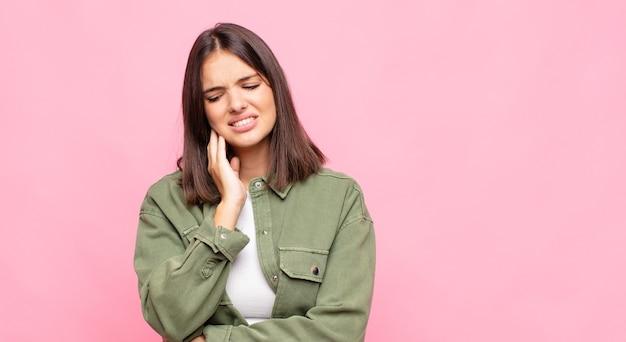 Mulher jovem e bonita segurando a bochecha e sofrendo de uma dor de dente dolorosa, sentindo-se doente, infeliz e infeliz, procurando um dentista