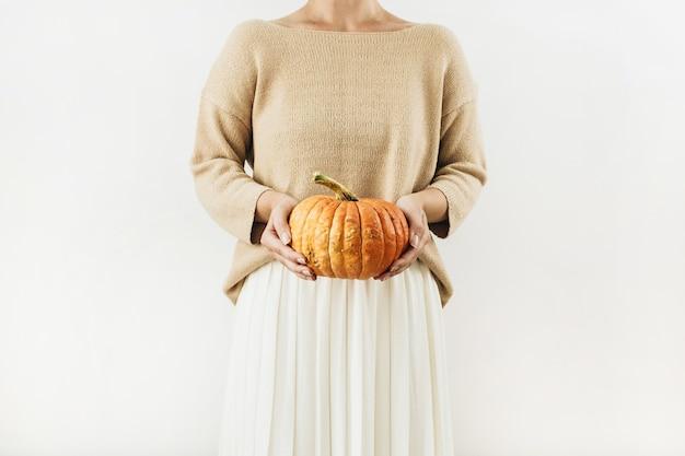 Mulher jovem e bonita segurando abóbora de halloween em uma superfície branca
