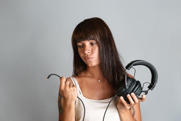 Mulher jovem e bonita segurando fones de ouvido e um fio com um conector na extremidade.