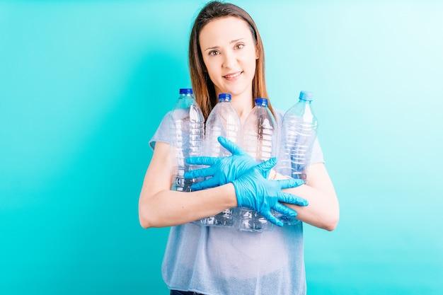 Mulher jovem e bonita segurando garrafas de plástico sobre fundo azul. conceito de reciclagem. cuidado ambiental
