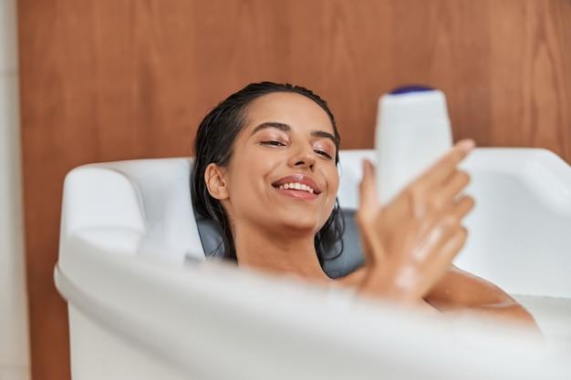 Mulher jovem e bonita segurando gel de banho enquanto toma banho
