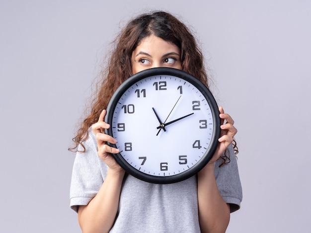 Mulher jovem e bonita segurando o relógio, olhando para o lado por trás dele, isolado na parede branca