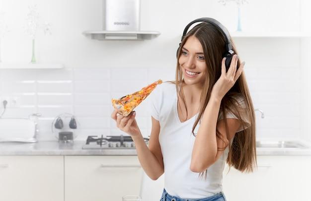 Mulher jovem e bonita segurando pizza na cozinha