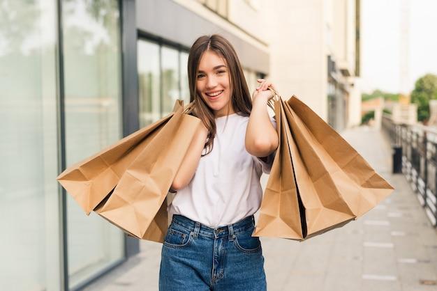 Mulher jovem e bonita segurando sacolas de compras e sorrindo ao ar livre