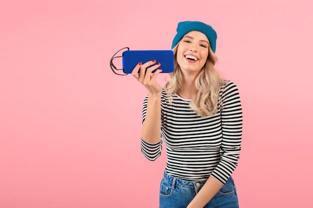 Mulher jovem e bonita segurando um alto-falante sem fio, ouvindo música, vestindo uma camisa listrada e chapéu azul, sorrindo, feliz humor positivo, posando em fundo rosa