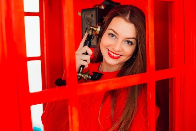 Mulher jovem e bonita segurando um aparelho antigo vintage em uma cabine vermelha