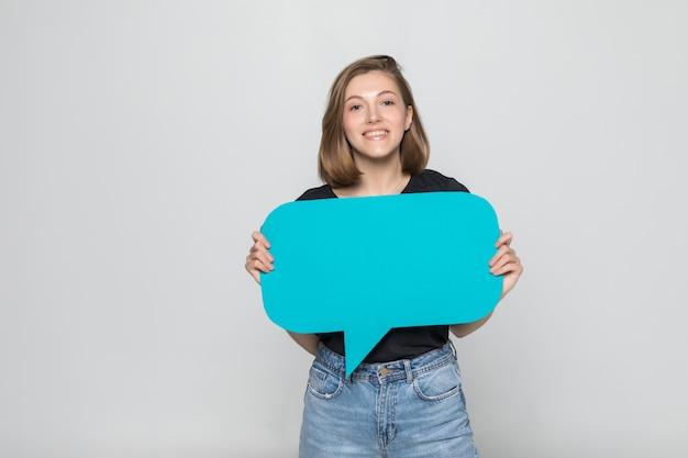 Mulher jovem e bonita segurando um balão de fala em branco sobre uma parede cinza