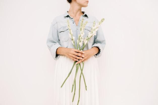 Mulher jovem e bonita segurando um buquê de flores brancas perto de uma parede branca