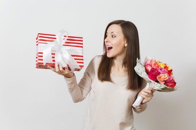 Mulher jovem e bonita segurando um buquê de flores lindas rosas, caixa de presente com presente isolado no fundo branco. copie o espaço para anúncio. conceito de são valentim ou dia internacional da mulher