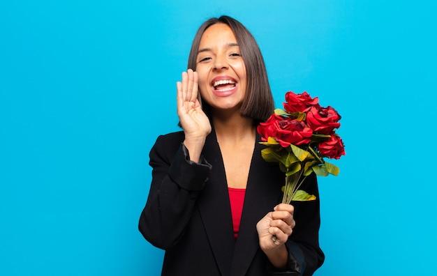 Mulher jovem e bonita segurando um buquê de rosas