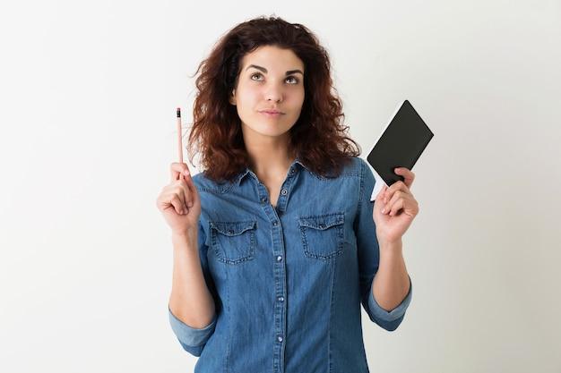 Mulher jovem e bonita segurando um caderno e um lápis, pensando, olhando para cima, tendo uma ideia, cabelo encaracolado, pensativo, isolado, camisa jeans azul, estilo hippie, aprendizagem do aluno, educação