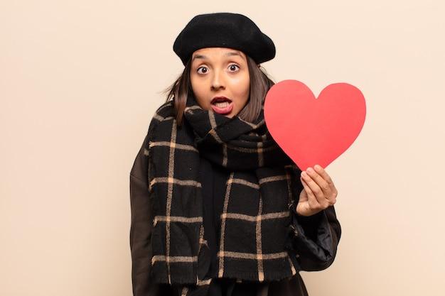 Mulher jovem e bonita segurando um cartão de coração
