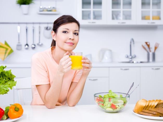 Mulher jovem e bonita segurando um copo de suco de laranja na cozinha