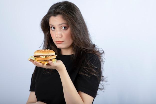 Mulher jovem e bonita segurando um delicioso hambúrguer de carne.