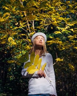 Mulher jovem e bonita segurando um galho com folhas amarelas