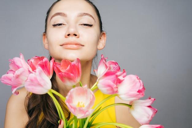 Mulher jovem e bonita segurando um grande buquê de flores, apreciando a fragrância