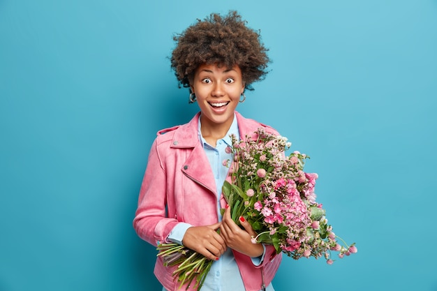 Mulher jovem e bonita segurando um grande ramo de flores perfumadas e comemora 8 de março vestida com uma jaqueta rosa isolada sobre a parede azul