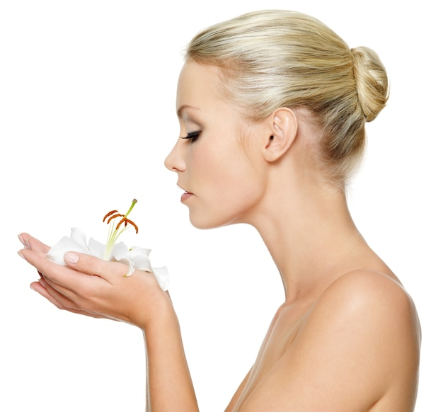 Mulher jovem e bonita segurando um lírio branco no rosto, isolado no branco