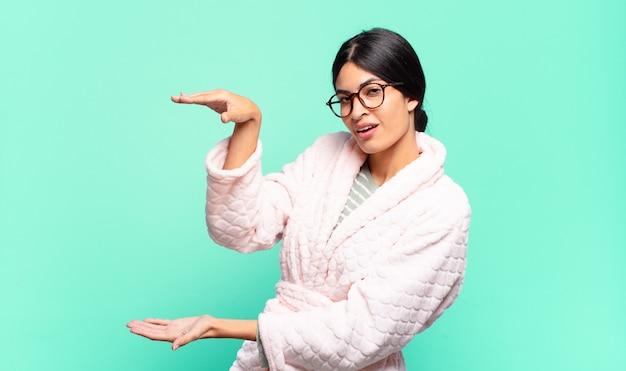 Mulher jovem e bonita segurando um objeto com as duas mãos no espaço lateral da cópia, mostrando, oferecendo ou anunciando um objeto. conceito de pijama