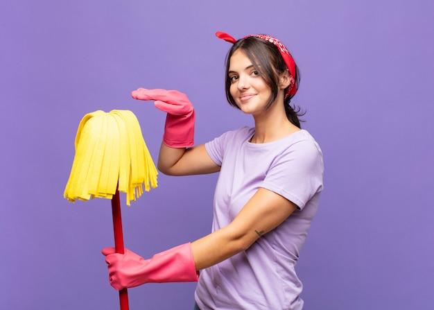 Mulher jovem e bonita segurando um objeto com as duas mãos no espaço lateral de cópia, mostrando, oferecendo ou anunciando um objeto