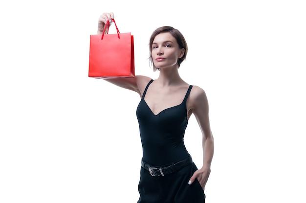 Mulher jovem e bonita segurando um pacote de artesanato vermelho na mão