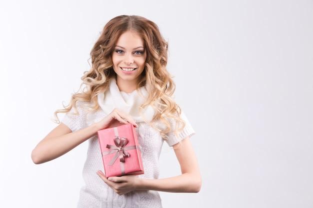 Mulher jovem e bonita segurando um presente em fundo branco.