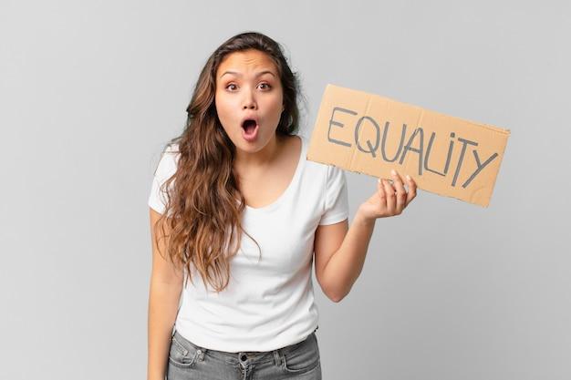 Mulher jovem e bonita segurando um quadro de igualdade