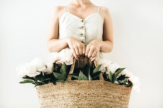Mulher jovem e bonita segurando um saco de palha com flores de peônia branca na superfície branca