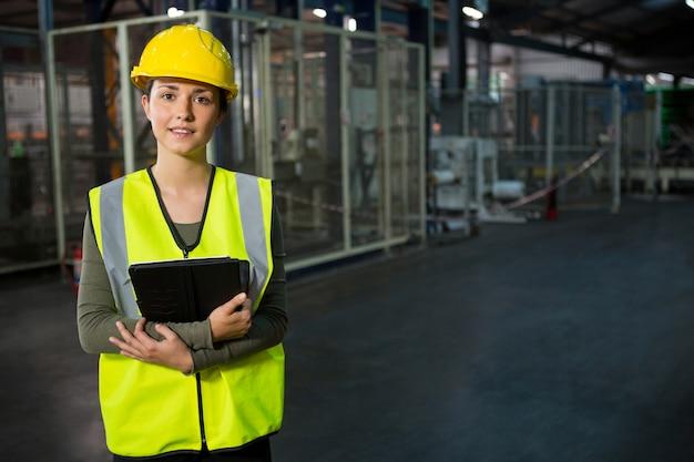 Mulher jovem e bonita segurando um tablet digital no armazém