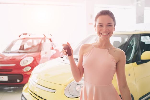 Mulher jovem e bonita segurando uma chave na concessionária de automóveis