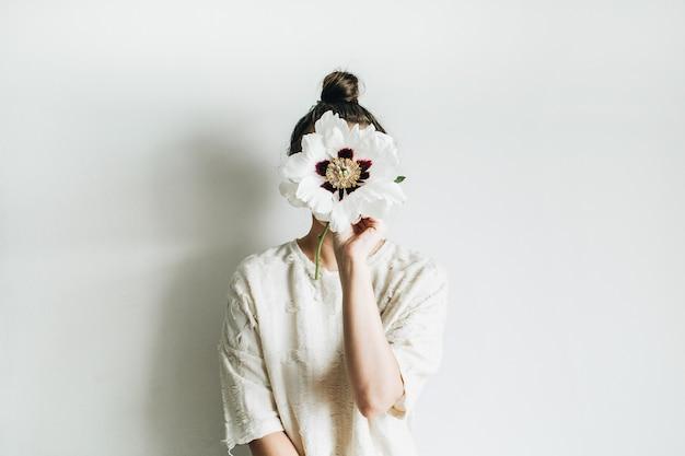 Mulher jovem e bonita segurando uma flor de peônia branca em fundo branco