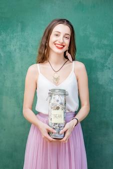 Mulher jovem e bonita segurando uma garrafa com economia de dinheiro para o pé de sonho sobre o fundo verde. conceito de economia para o futuro
