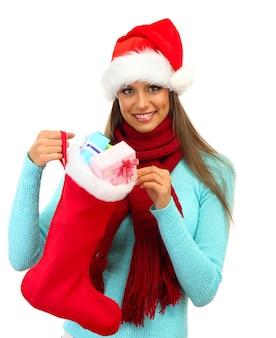 Mulher jovem e bonita segurando uma meia de natal com presentes, isolado no branco