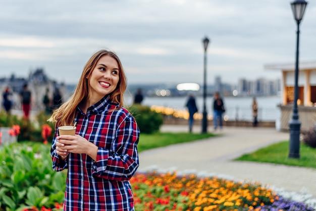 Mulher jovem e bonita segurando uma xícara de café e sorrindo