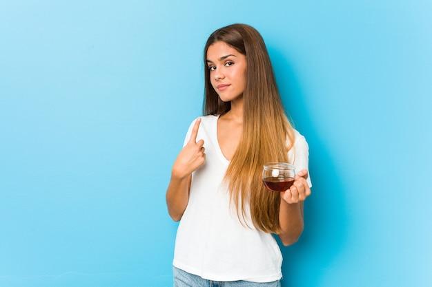 Mulher jovem e bonita segurando uma xícara de chá, apontando com o dedo para você, como se fosse um convite para se aproximar.