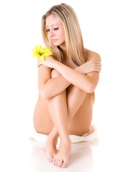 Mulher jovem e bonita sem roupas com uma flor no cabelo, posando em um fundo branco. conceito de mulher jovem bem cuidada e tratamentos de beleza